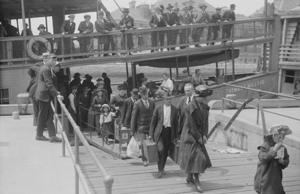 Immigrants arrive at Ellis Island in Upper New York Bay around 1900. In 1924, the U.S. would restrict immigration based on national origin. Forty years after that, it eliminated those restrictions.