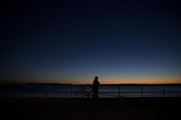 <p>Eric Shalit watches the sunset during a bike ride on Tuesday, December 5, 2017, in West Seattle.</p>