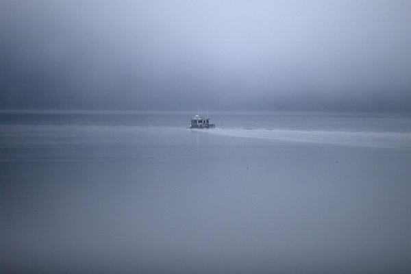 <p>A boat is shown through the morning fog on Wednesday, December 6, 2017, during a King Tide in Olympia. </p>