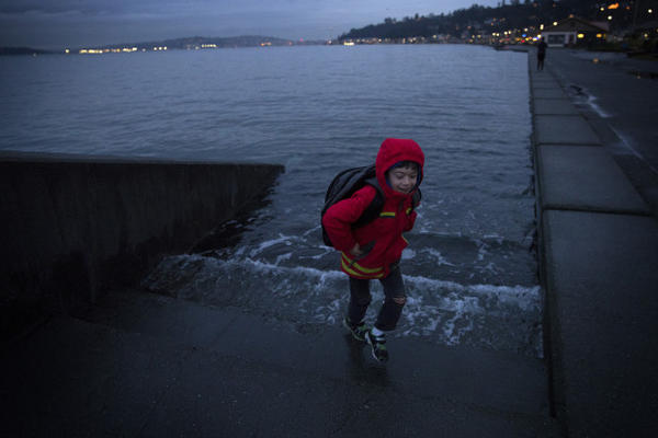 <p>Ely Thomas, 7, runs from water spilling over stairs during a King Tide at Alki Beach Park on Friday, January 5, 2018, in West Seattle. </p>