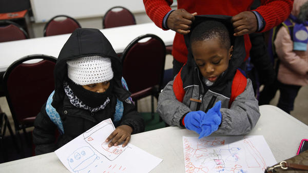 Teacher Loraine Wilson, top right, helps bundle up pre-kindergarten students as they wait to be picked up at the end of a school day at Lakewood Elementary School in Baltimore on Jan. 9. The day before, Lakewood students were sent back home just after arriving when pipes burst in the school.