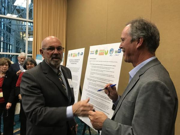 Monroe County Mayor David Rice, left, and Broward County Mayor Beam Furr were among officials and business leaders who signed an agreement to collaborate on climate issues at a regional summit in December 2017.