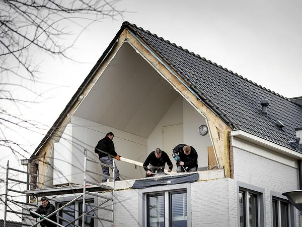 Builders fix the side wall of a house after it was blown away in De Meern, Netherlands. More than 260 flights were canceled at Schiphol airport in Amsterdam.