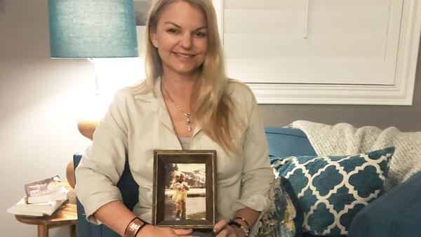 "Christine Caria in her home, holding a picture of her as a child in Lake Tahoe. It's her ""happy place"" that she thinks of when traumatic thoughts get into her head."