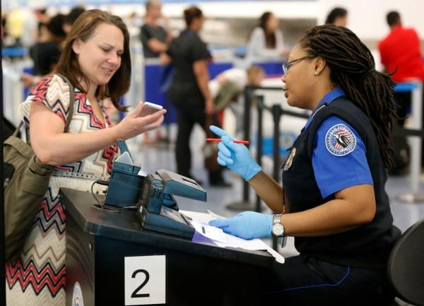 <p>A TSA officer looks on as a traveler scans her boarding pass on her phone, Tuesday, May 2, 2017, at Miami International Airport in Miami.</p>