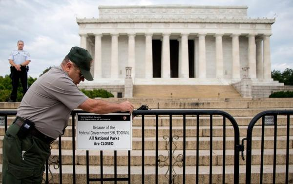 <p>In this Oct. 1, 2013, file photo, A U.S. Park Police officer watches at left as a National Park Service employee posts a sign on a barricade closing access to the Lincoln Memorial in Washington.</p>