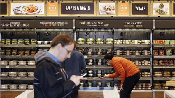 Shoppers roam through an Amazon Go store in April. The automated grocery, which had been restricted to Amazon employees, will be open to the public starting Monday.
