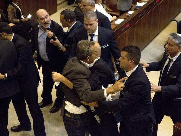Israeli Arab parliamentarians and other members of the Knesset scuffle with security after they held protest signs during Monday's speech by Vice President Pence.