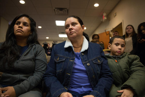 Hurricane evacuees Yara Vasquez (left) and Wanda Ortiz (center) watch a press conference at the hotel they've been living in with their families under a FEMA program on January 19, 2018.