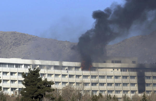 Men try to escape from a balcony of the Intercontinental Hotel on Sunday after an attack in Kabul, Afghanistan.