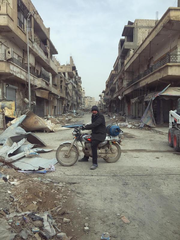 A man rides through Raqqa, Syria, on his motorbike.