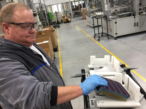 <p>John Clason loads solar cells into a tray to be made into panels at the SolarWorld Americas manufacturing plant in Hillsboro.</p>