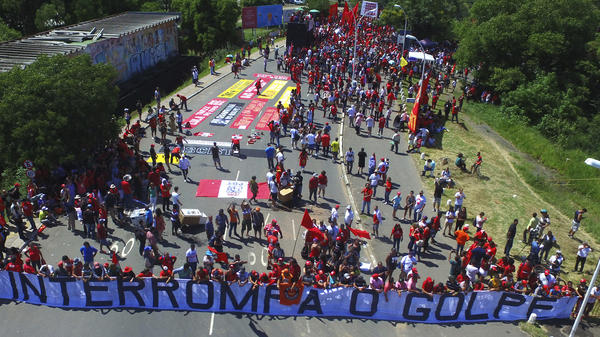"Lula's supporters hold a banner that reads, in Portuguese, ""Stop the Coup."" The demonstrators had gathered Wednesday near the court in Porto Alegre, Brazil, where judges ruled unanimously to uphold the former president's graft conviction."