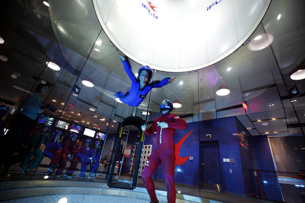"Kailey Looney, a fifth-grader at Camacho Elementary School,""flies"" with the help of instructor Greg Levin at iFly Austin, an indoor skydiving facility, on Wednesday."