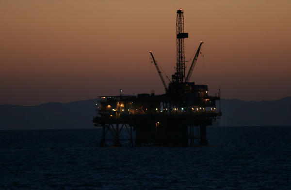 <p>An oil rig lighting up for the night shift off the coast of Southern California. Catalina Island is just barely visible in the background.</p>