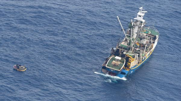This photo released by the New Zealand Defense Force shows a dinghy, left, carrying seven survivors from a missing ferry and a fishing boat in the Pacific Ocean on Sunday.