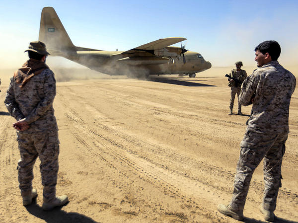Saudi soldiers stand by as a Saudi Air Force cargo plane carrying humanitarian aid lands at an airfield in Yemen's Marib province on Friday. The Saudi-led coalition, which has led a years-long airstrike campaign supported by the U.S., has also pledged $1.5 billion in new aid.