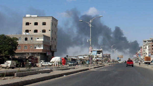 Smoke reaches skyward Tuesday in Aden, the Yemeni government's de facto capital. Since clashes began between government forces and southern separatists Sunday, several dozen people have died and dozens more have been injured.