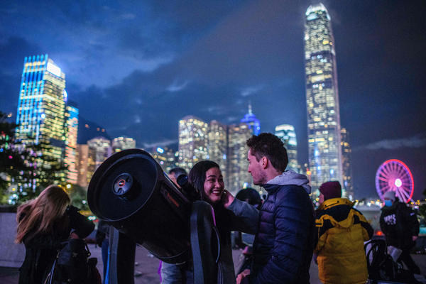 People set up telescopes near Victoria Harbour in hopes of seeing a supermoon on a cloudy evening in Hong Kong.