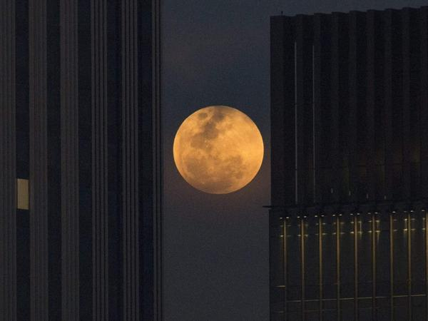 The moon rises between two office buildings in Bangkok, Thailand.