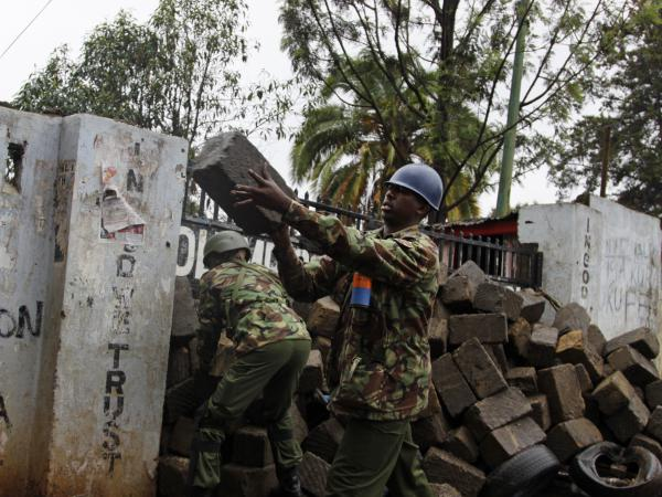 Police dismantle a barricade set-up by protesters in the Kibera slum in Nairobi on Thursday.