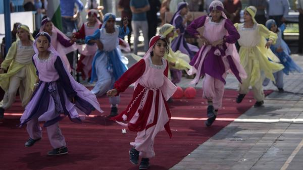 The U.S. says it's sending money to sustain schools and health services for Palestinian refugee. In this 2016 photo, schoolgirls dance at a summer camp organized at a U.N. Relief and Works Agency school in Gaza City.