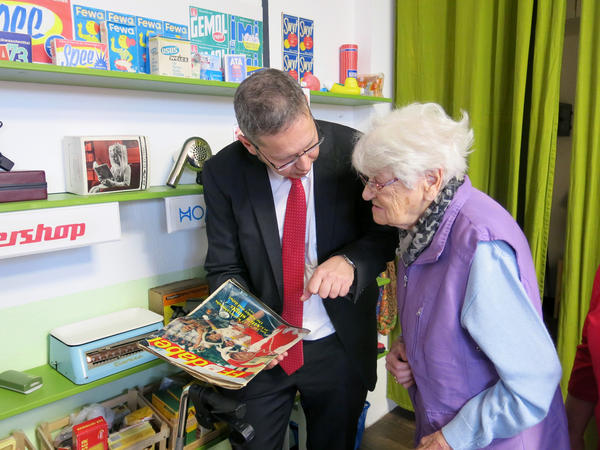 """AlexA Residence for Senior Citizens Director Gunter Wolfram, 49, shows resident Gerda Noack, 93, an old East German variety magazine. It's one of many communist-era items available to dementia patients to touch and look at in two """"remembrance rooms"""" at this Dresden nursing home."""