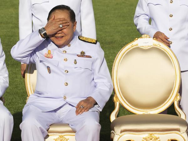 Deputy Prime Minister Prawit Wongsuwan raises his hand to shade the sun, revealing a luxury watch and diamond ring, during a Dec. 4 ceremony at Government House. The expensive jewelry set off an outraged reaction in Thailand.