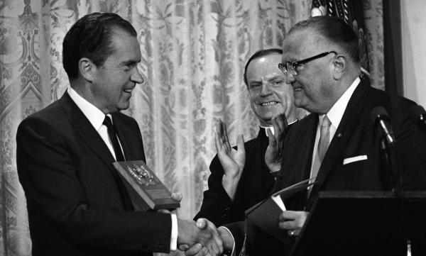 In 1969, FBI Director J. Edgar Hoover presents a gold badge to President Richard Nixon, making him an honorary member of the agency, during graduation ceremonies for the FBI National Academy.