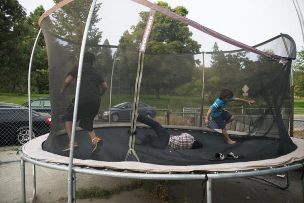 Tres de los hijos de Manuel y de V en el trampolín, en el patio trasero. Manuel estuvo lejos de su familia durante seis meses.
