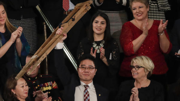 North Korean defector Ji Seong Ho holds up his crutches after his introduction by Trump. He was one of 16 audience members acknowledged by the president.