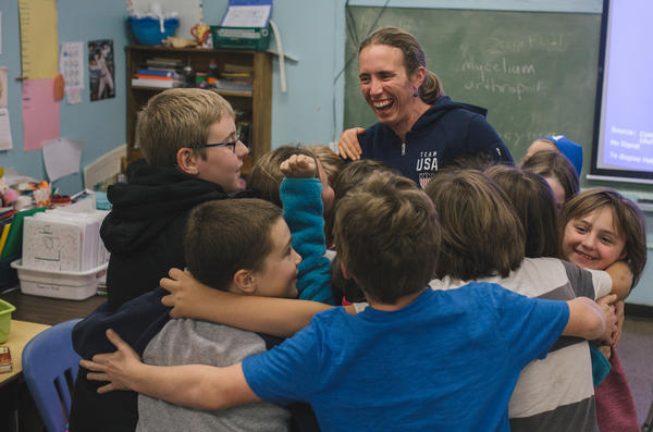 Susan Dunklee receives a group hug from third and fourth grade students after giving a presentation about biathlon at the Craftsbury Elementary School in Vermont.