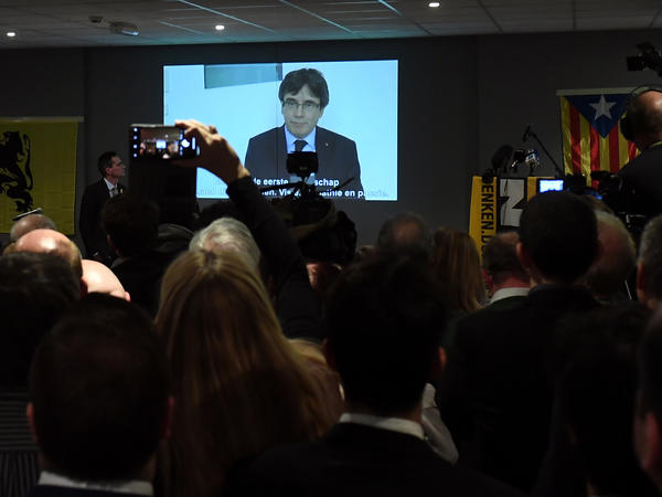 People watch a live broadcast of a speech on Tuesday by ousted Catalan separatist leader Carles Puigdemont from Leuven, Belgium.