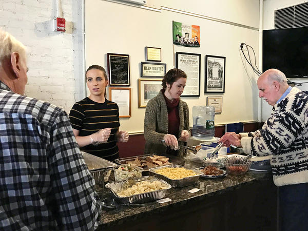 """Erica Paul (left) and Danielle Gallagher serve lunch to John Houlihan and other seniors attending the New York Irish Center's Wednesday Lunch Club in Queens, N.Y. On a wall of historical memorabilia hanging behind them is an old sign saying """"HELP WANTED, NO IRISH NEED APPLY."""""""
