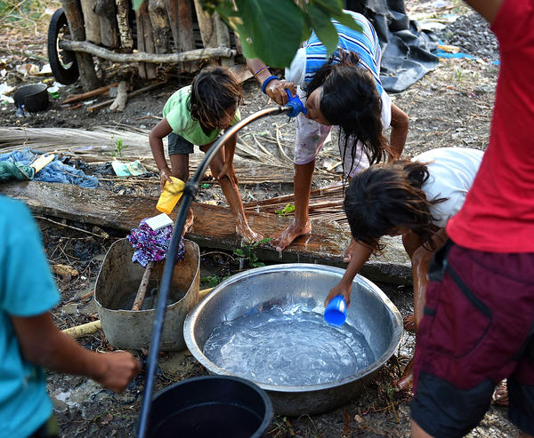 Children drinking from a makeshift water pipe in a village in the Mindanao island in the Philippines.