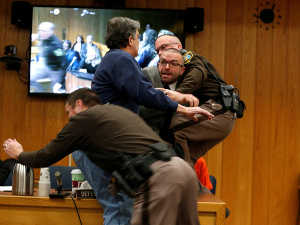 Randall Margraves (in blue sweatshirt) lunges at Larry Nassar (in orange) during Nassar's sentencing hearing in Michigan's Eaton County Circuit Court on Friday. A former USA Gymnastics team doctor, Nassar pleaded guilty in November to sexual assault charges.