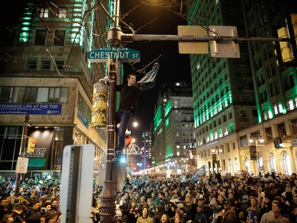 A man climbs a traffic pole as Philadelphia Eagles fans celebrate victory in Super Bowl LII against the New England Patriots Sunday evening.