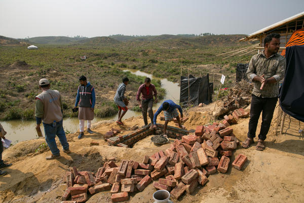 Men build a brick and cement toilet in the Kutupalong refugee camp. The new toilet will replace the open-pit toilets — covered with plastic for privacy — that can be seen in the background.