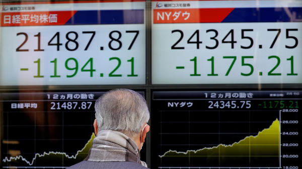 A man looks at an electronic stock indicator of a securities firm in Tokyo, on Tuesday. Shares tumbled in Asia on Tuesday after a wild day for U.S. markets that resulted in the biggest drop in the Dow Jones industrial average in six and a half years.