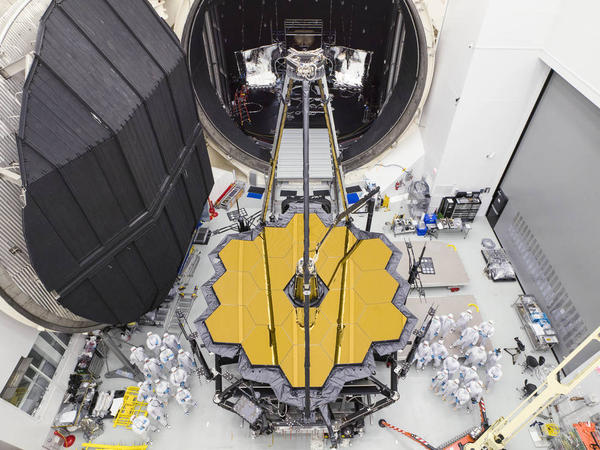 Engineers next to NASA's James Webb Space Telescope at NASA's Johnson Space Center in Houston.