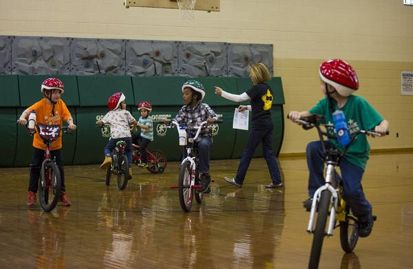 Children take test rides on their newly acquired bicycles in the gymnasium of the Stephanik School . (Jesse Costa/WBUR)