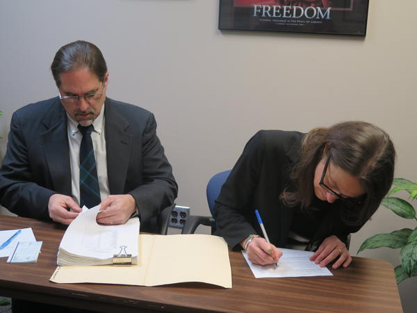 Constance Gudell Newton (right) signs paperwork at Ohio Secretary of State's office