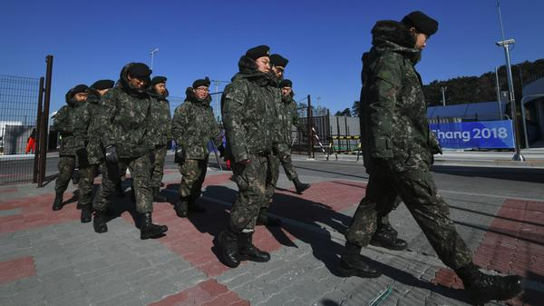 South Korean soldiers walk past a security checkpoint Tuesday in Pyeongchang, where they have been replacing security guards who showed symptoms of the norovirus.