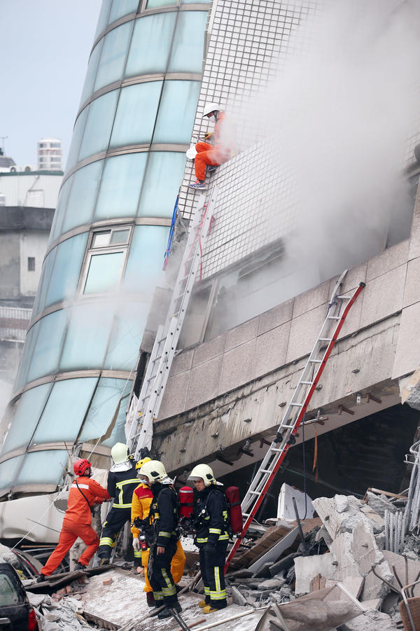 Rescue workers search for survivors in a damaged building on Wednesday, bracing themselves for the aftershocks that continued to rattle Taiwan after the deadly earthquake.