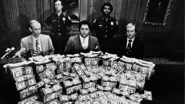In 1981, Atlanta Mayor Maynard Jackson is flanked by security guards in his office as he poses with $100,000 in reward money offered for clues to the deaths of 17 Atlanta children.