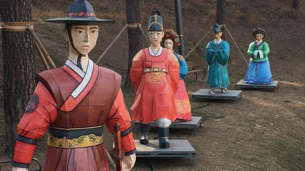 "Figures in traditional dress line a hillside across the street from the Olympic Park in ""sub-host"" city Gangneung."