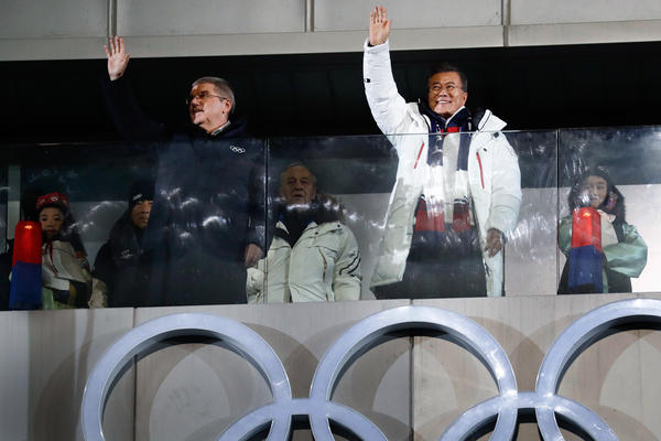President of the International Olympic Committee Thomas Bach (left) and South Korea's President Moon Jae-in (center) wave during the opening ceremony.
