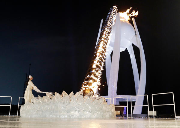 A torchbearer lights the Olympic flame.