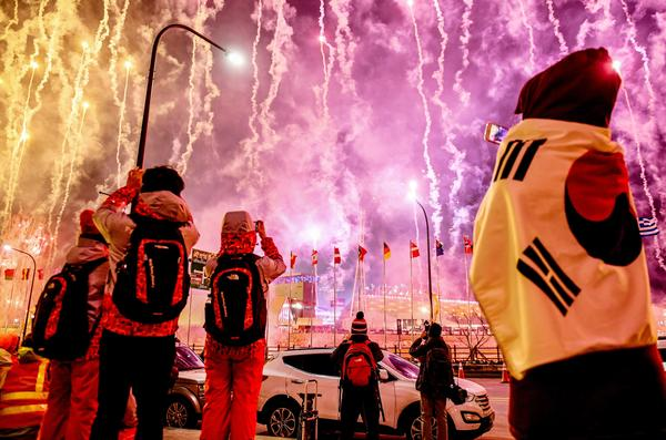 Spectators watch fireworks go off at the start of the opening ceremony.