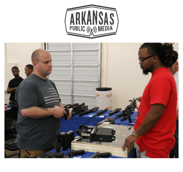 John Fulbright (left) shows a gun to a potential customer at a gun show in Little Rock on Sunday.